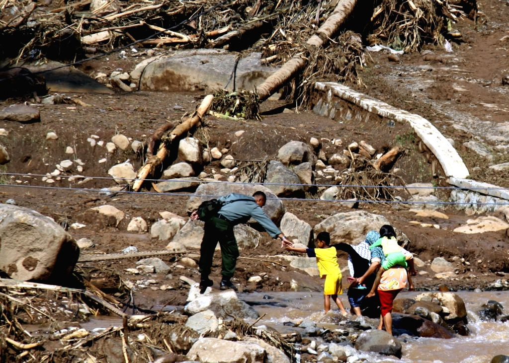 WEST JAVA, May 25, 2016 - People cross a dried river to see houses there after floods and landslide hit a village in Subang, West Java, Indonesia, May 24, 2016. The casualty number of flash floods ...