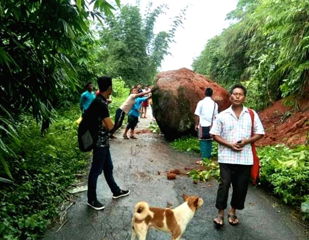 West Karbianglong: People try to push aside a boulder that had fallen during a landslide and blocked a road in Assam's West Karbianglong district, on July 25, 2019. (Photo: IANS)