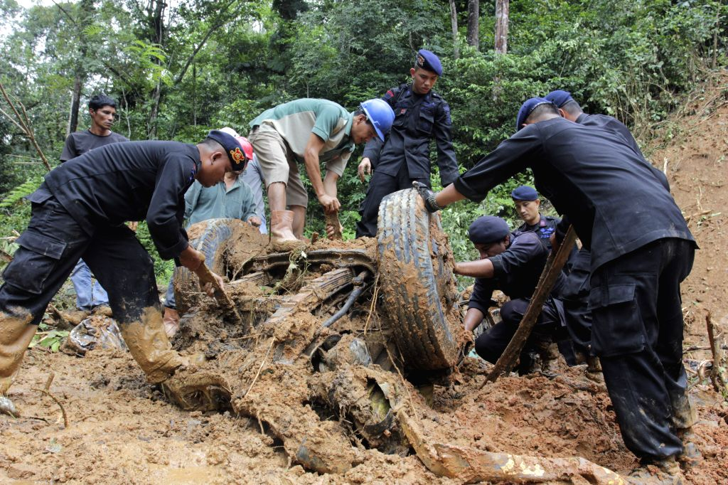 WEST SUMATRA, March 4, 2017 - Police officers dig out bodies buried inside a vehicle under mud and rock after hit by flood and landslides at Koto Alam village of Limapuluh Kota district in West Java, ...