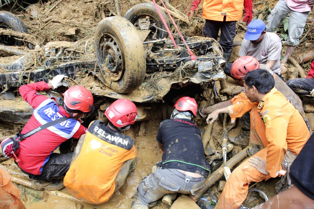 WEST SUMATRA, March 4, 2017 - Search and rescue team try to dig out bodies buried inside a vehicle under mud and rock after hit by flood and landslides at Koto Alam village of Limapuluh Kota district ...