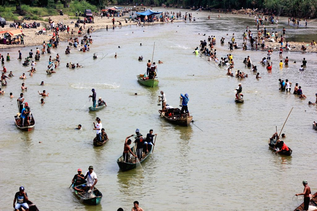WEST SUMATRA, Sept. 15, 2019 - People catch fish during Ikan Larangan harvest festival at Nagari Aia Gadang, West Sumatra, Indonesia, Sept. 15, 2019.