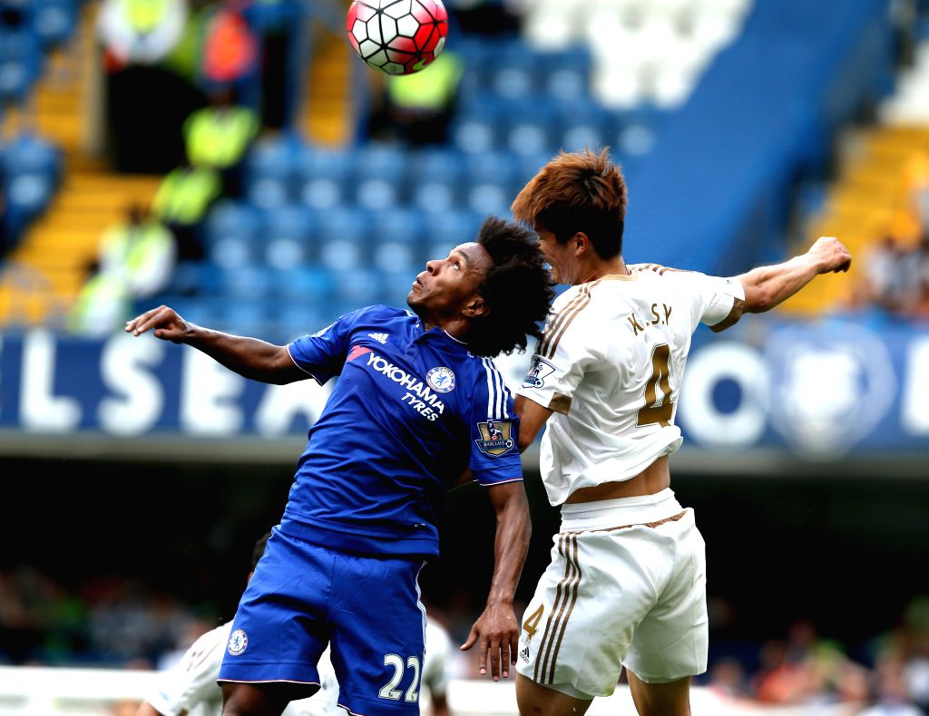William (L) of Chelsea heads for the ball with Ki Sung-yueng of Swansea City during the Barclays Premier League match between Chelsea and Swansea City at the Stamford ...