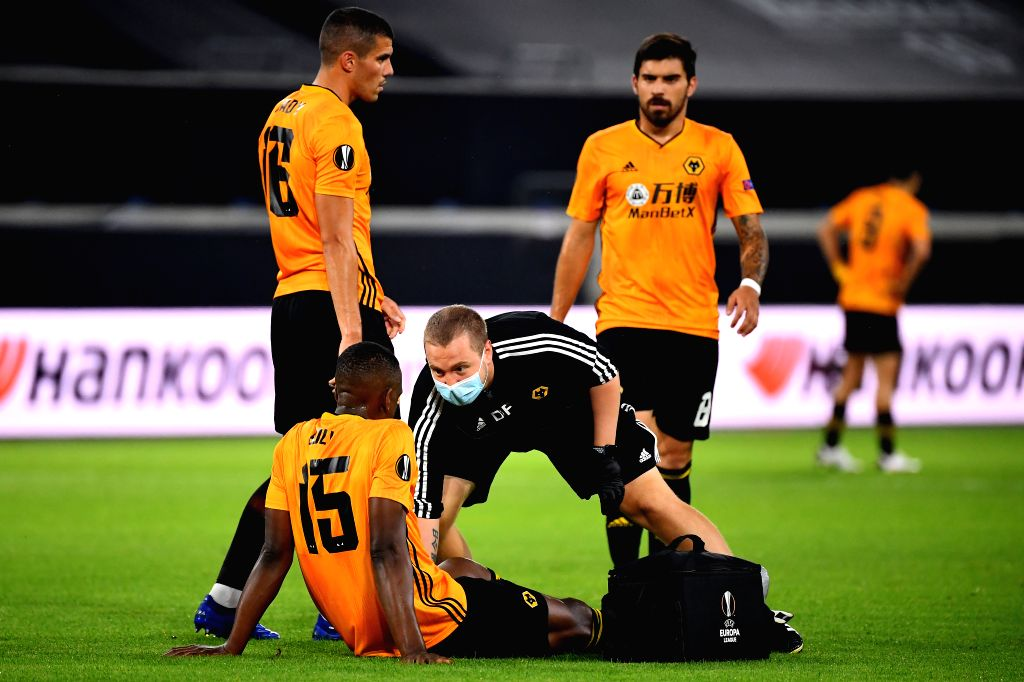 Willy Boly (bottom) of Wolverhampton Wanderers receives medical treatments during the UEFA Europa League quarterfinal between Wolverhampton Wanderers and Sevilla ...
