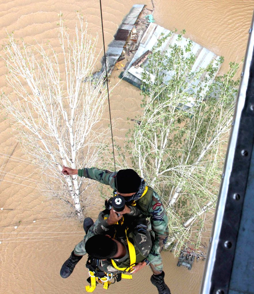 Winching operation from an IAF helicopter to rescue people stranded on rooftops, in Srinagar on September 09, 2014.