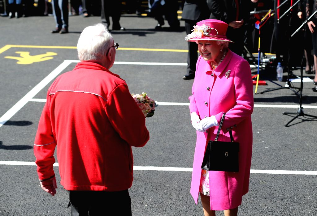 WINDSOR, April 20, 2016 - Queen Elizabeth II (R) receives a bouquet from Bob Hartley, the currently Royal Mail's longest serving employee, during a celebration to mark the 500th anniversary of the ...