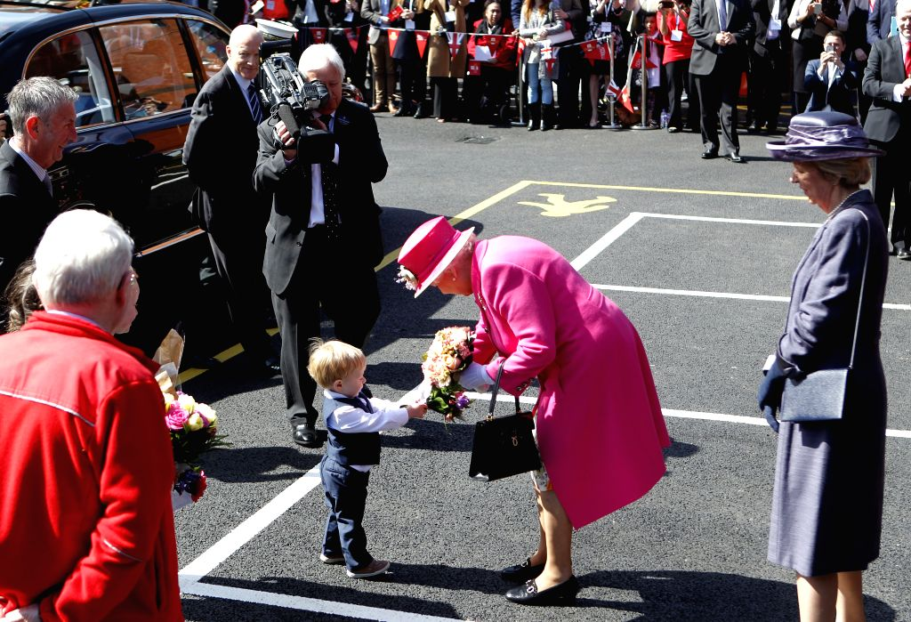 WINDSOR, April 20, 2016 - Queen Elizabeth II receives a bouquet from a boy during a celebration to mark the 500th anniversary of the Royal Mail postal service at the Royal Mail Delivery Office in ...