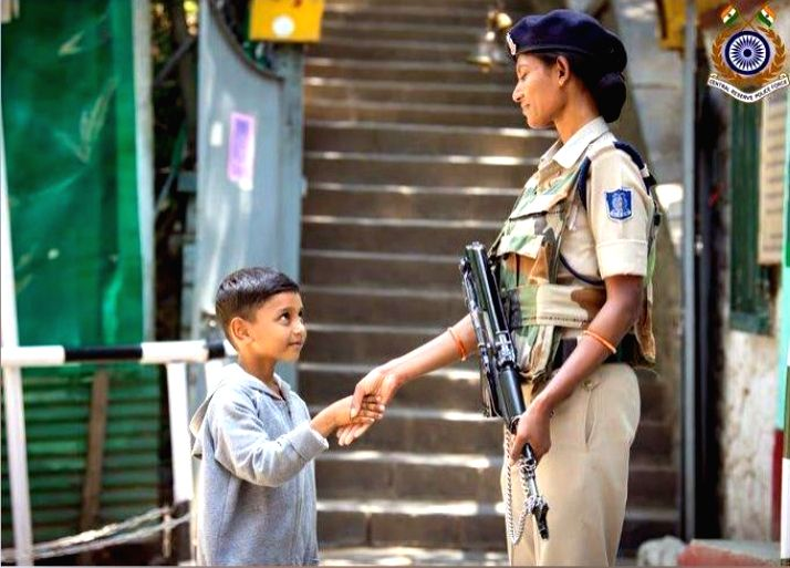 Woman CRPF personal shaking hands with kid in Kashmir.