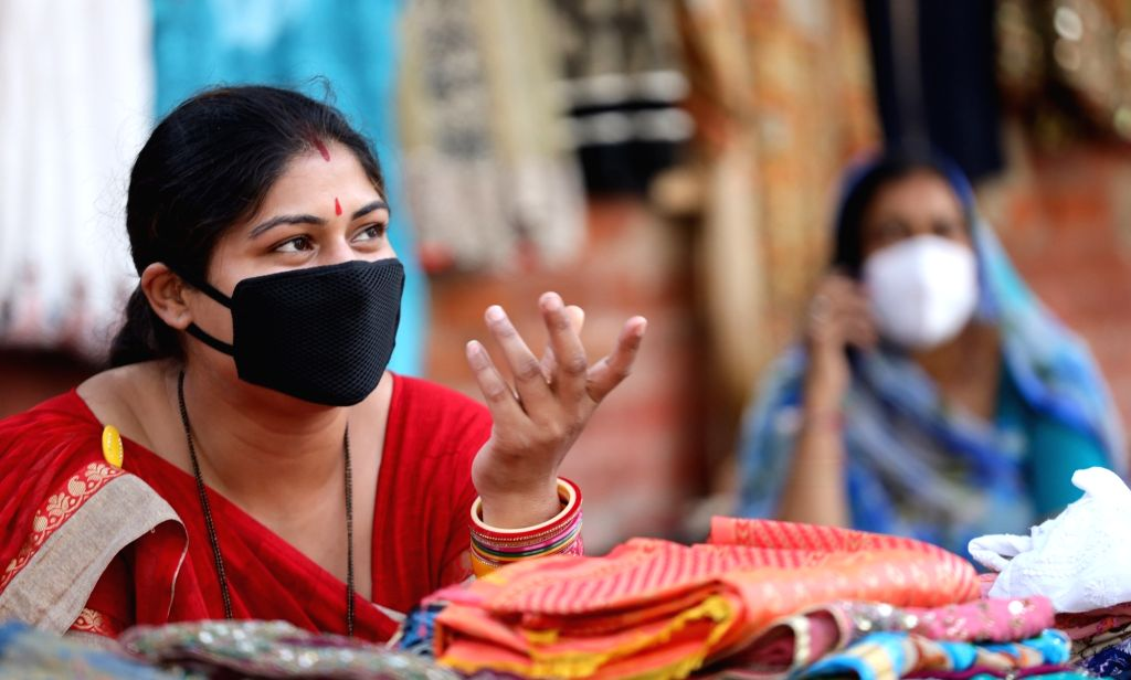 Woman shopkeeper in Delhi promotes the use of masks and sanitisers amid outbreak of coronavirus, in New Delhi on 19 March 2020.