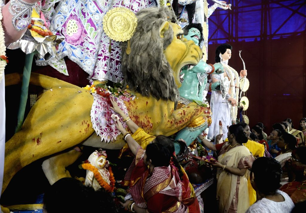 Women apply vermilion to the idol of Goddess Durga as they celebrate 'Sindoor Khela' on Vijayadashami, in Kolkata on Oct 8, 2019.