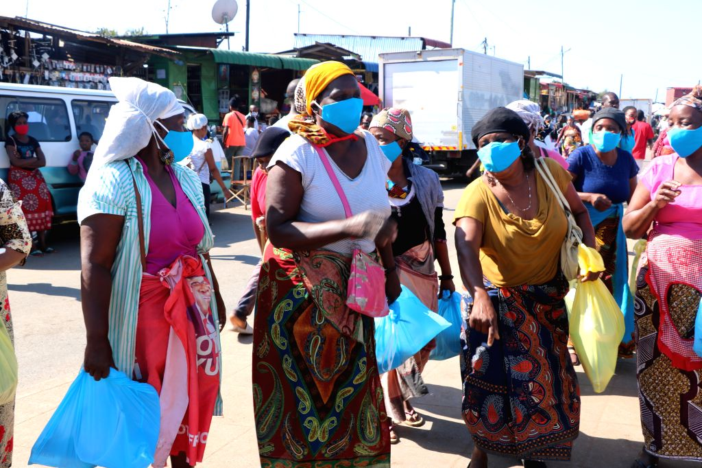 Women attend a face mask distribution ceremony in Maputo, Mozambique, on July 31, 2020. The government of Maputo distributed some 13,000 face masks to 4,500 ...
