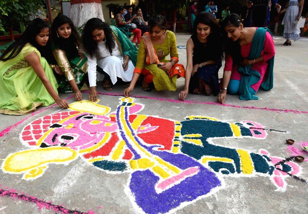 Women busy making 'rangoli' ahead of Diwali in Patna on Nov 5, 2018.