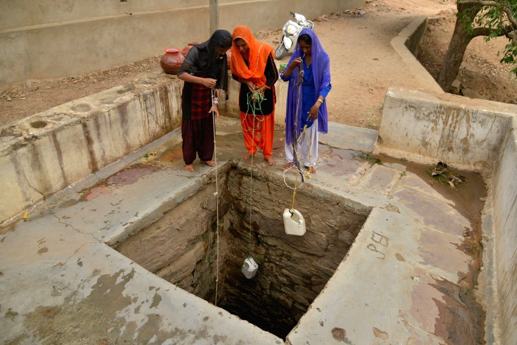 Women collect drinking water from a well on the outskirts of Ajmer amid scarcity of drinking water, on June 13, 2019.