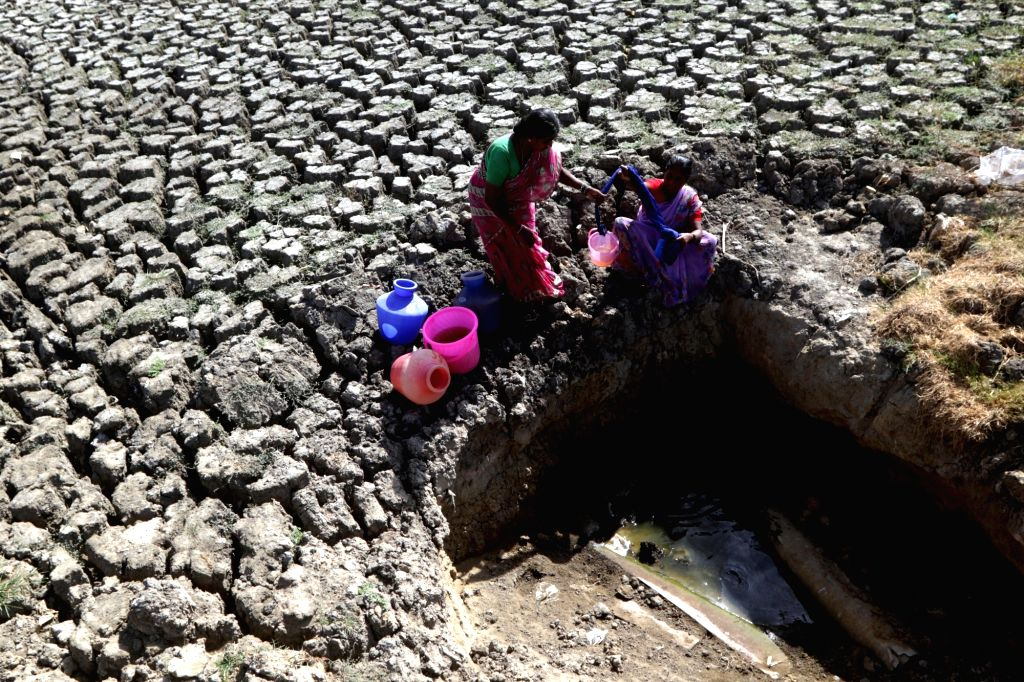 Women collect water from an opening made by locals by digging up a dried-up lake, amid scarcity of water in Chennai, on June 13, 2019.