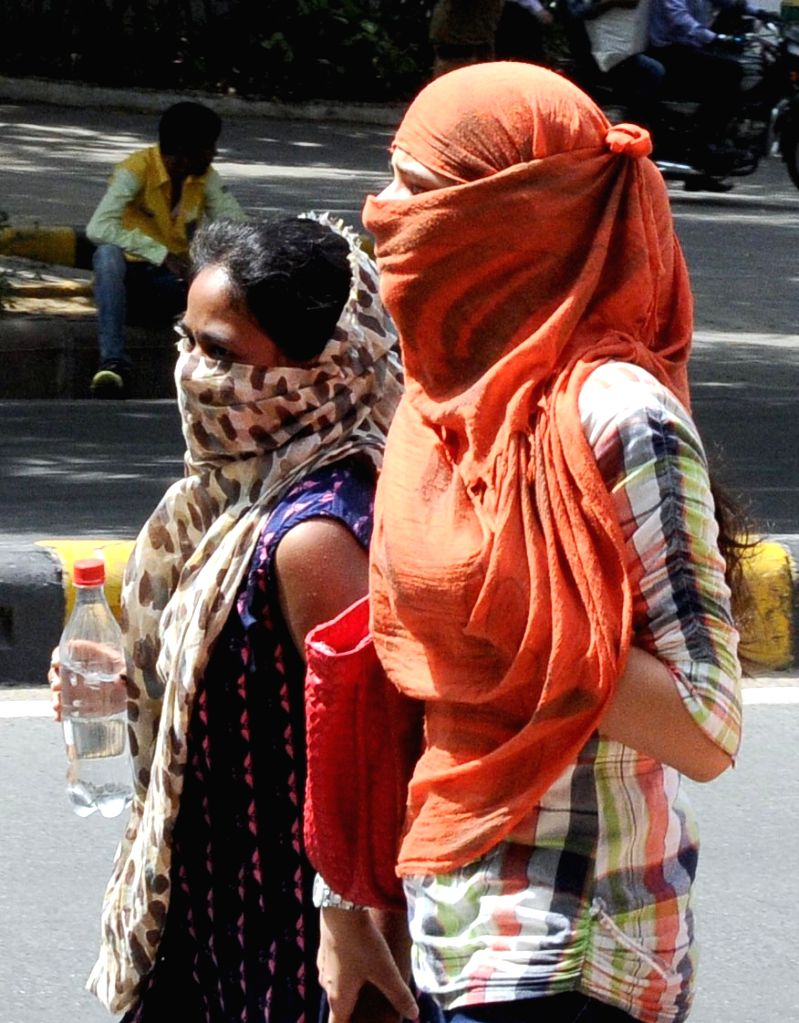 Women cover their faces to avoid direct contact with sun as mercury begins to rise in New Delhi on April 22, 2016.
