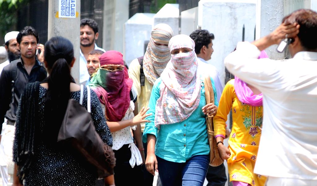 Women cover their faces to protect themselves from scorching heat in New Delhi on May 7, 2014.