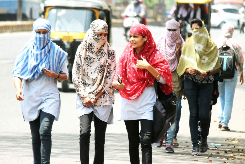 Women cover their faces to protect themselves from the scorching heat on a hot summer day, in Nagpur on April 4, 2018.
