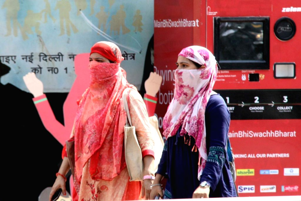 Women cover themselves to avoid scorching sun on a hot summer day in New Delhi on June 14, 2019.