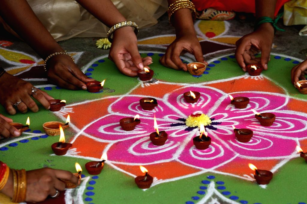 Women decorate 'rangoli' with earthen lamps as they participate in Diwali celebrations ahead of the festival in Chennai on Oct 25, 2019.