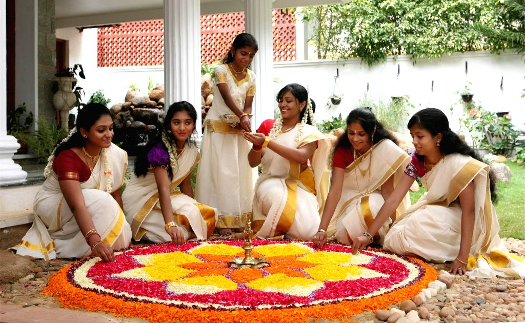 Women decorating Rangoli with flowers, on the eve of Onam Festival, in Bangalore on Sept. 6,  2014.