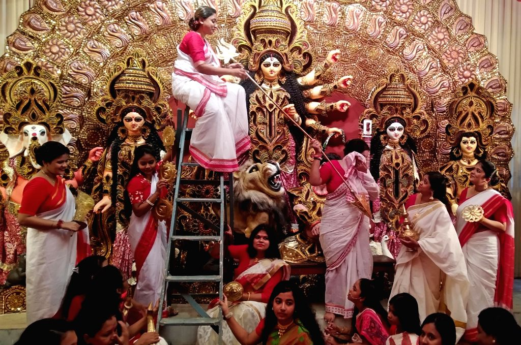 Women devotees decorate goddess Durga at a Community puja pandal ahead of Durga puja Festival in Kolkata on Tuesday October 05 ,2021.