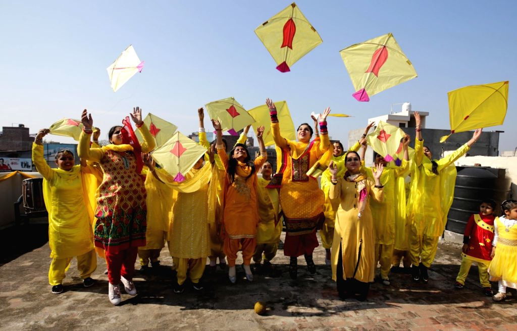 Women dressed in yellow take part in kite flying on the eve of Basant Panchami festival in Amritsar, on Feb 9, 2019.