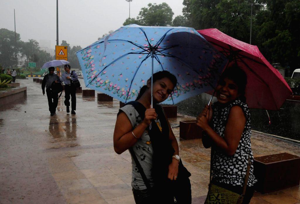 Women enjoy rains in New Delhi on Sept 3, 2014.