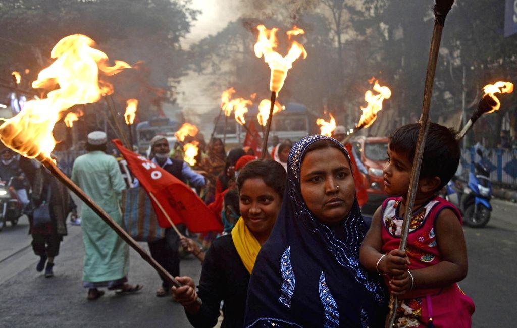 Women farmers in a torch light rally observe 'Mahila Kisan Diwas' to protest against Farm law in Kolkata on Jan 18, 2021.
