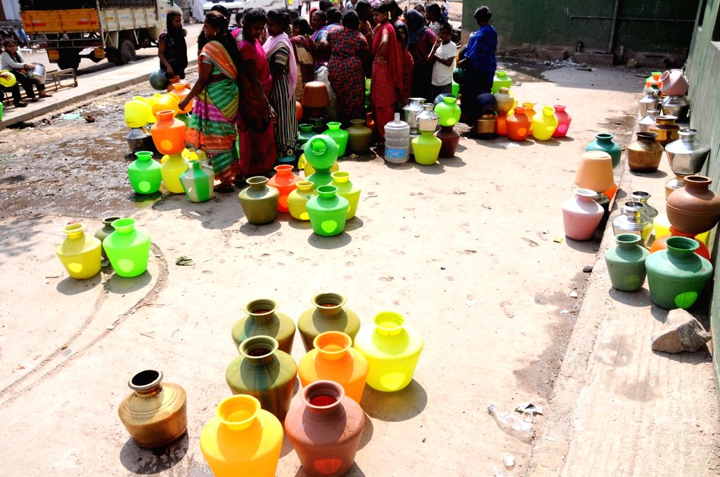 Women gather around roadside taps with their plastic water pots to collect water, in Bengaluru on March 22, 2018. March 22 is observed as World Water Day.