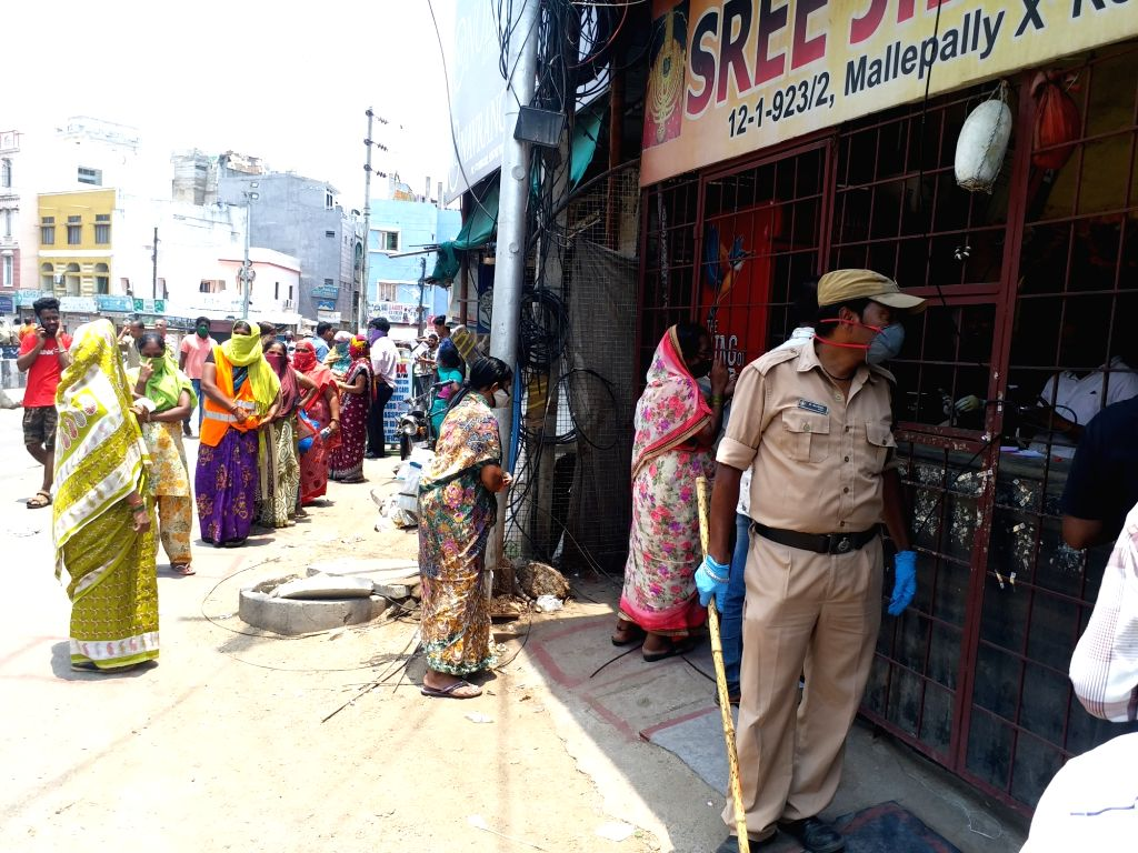 Women gather in long queues to purchase liquor at a wine and beer shop at Hyderabad's Banjara Hills during the extended nationwide lockdown imposed to mitigate the spread of coronavirus, ...