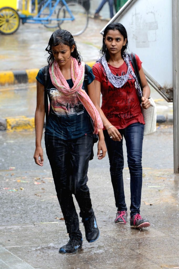 Women get drenched during rains in New Delhi on Aug 28, 2014.