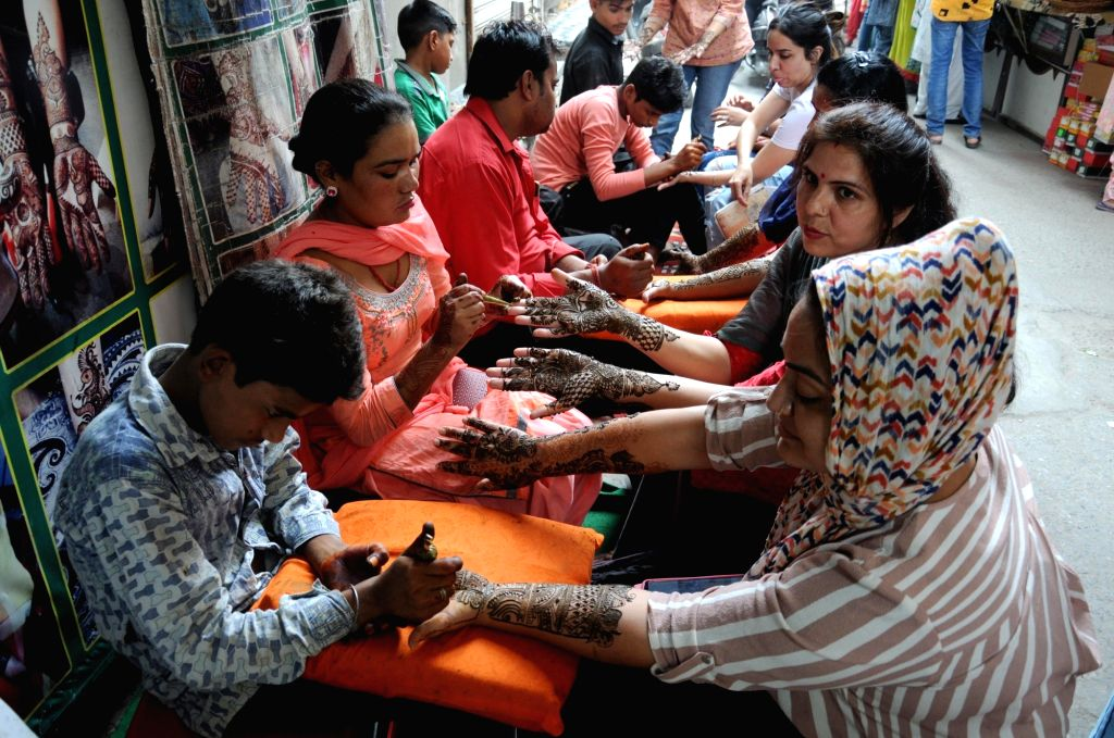 Women get henna applied on her palms ahead of Karva Chauth celebrations, in Amritsar on Oct 16, 2019.