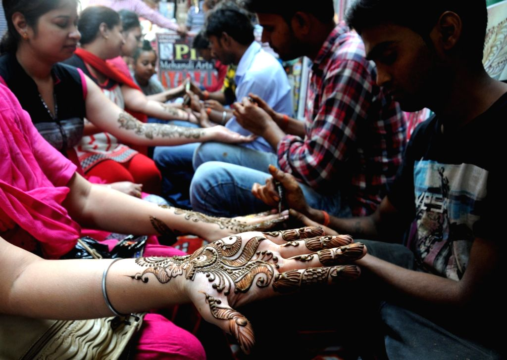 Women get mehndi applied on their palm on the eve of Karva Chauth in Amritsar, on Oct 18, 2016.