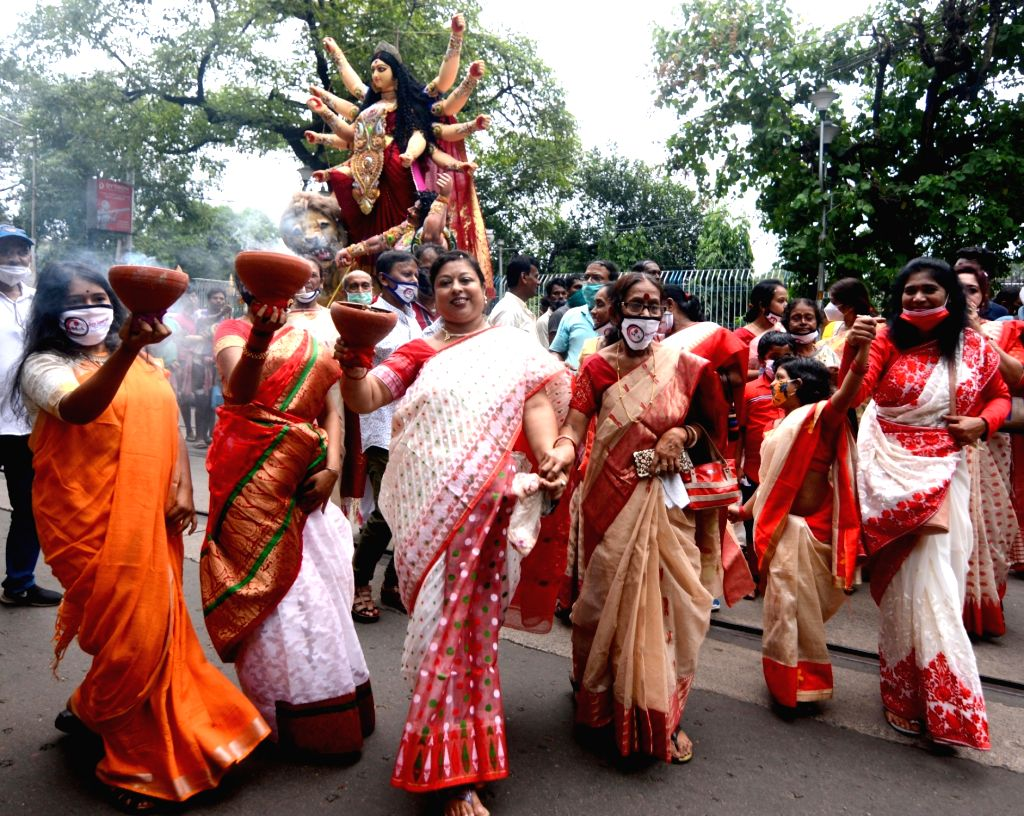 Women holding a Dhunochi and performs dance to bringing an Idol of Goddess Durga to their community Puja pandel from Kumortuli workshop in Kolkata on Tuesday October 05 ,2021.