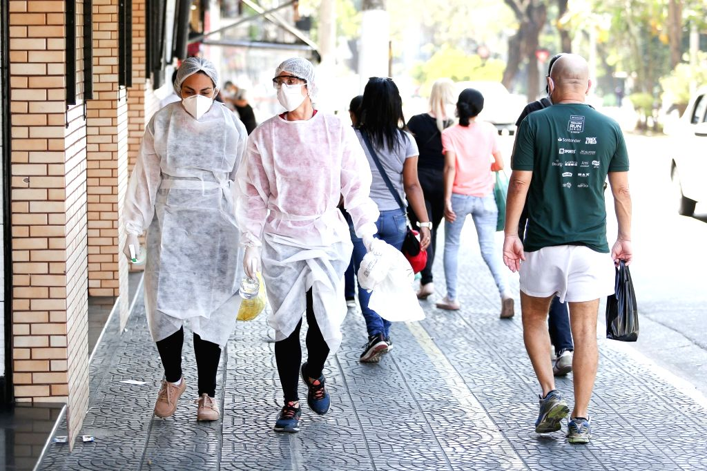 Women in protective suits walk on the street in Sao Paulo, Brazil, Aug. 12, 2020.   Brazil on Wednesday said it registered 1,175 deaths from the novel coronavirus ...