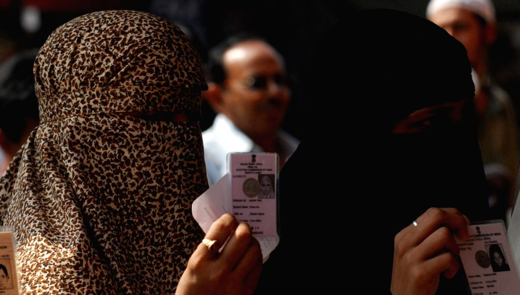 Women in queue, displaying their voter id Cards in Kolkata on Parliamentary Election day on 13th May 2009.