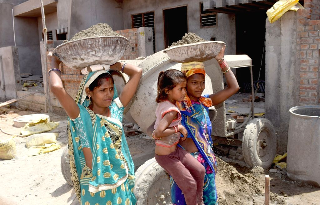 Women labourers carry cement on their heads at a construction site in Uttar Pradesh's Mathura, on May 1, 2019. May 1 is observed as International Labor Day.