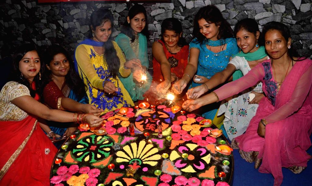 Women make rangoli at their homes on Dhanteras in Patna on Oct 28, 2016.