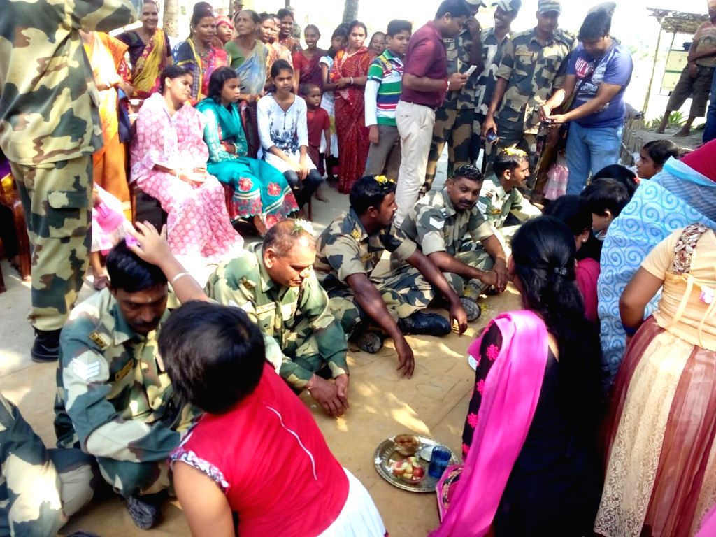 Women mark the foreheads of soldiers with sandalwood paste on Bhai Phonta - a Hindu festival where the sisters pray for safety, well being and success of their brothers -  in Balurghat, ...