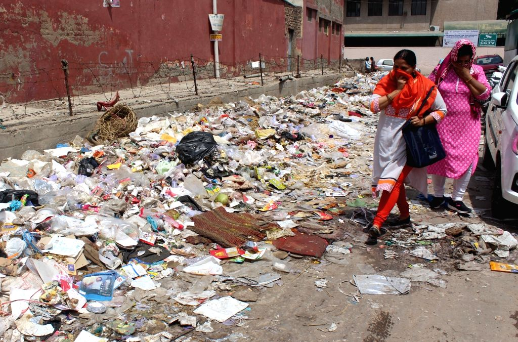 Women pass by a heap of garbage that lay unattended as sanitation workers continue their strike in Gurugram on May 21, 2018.