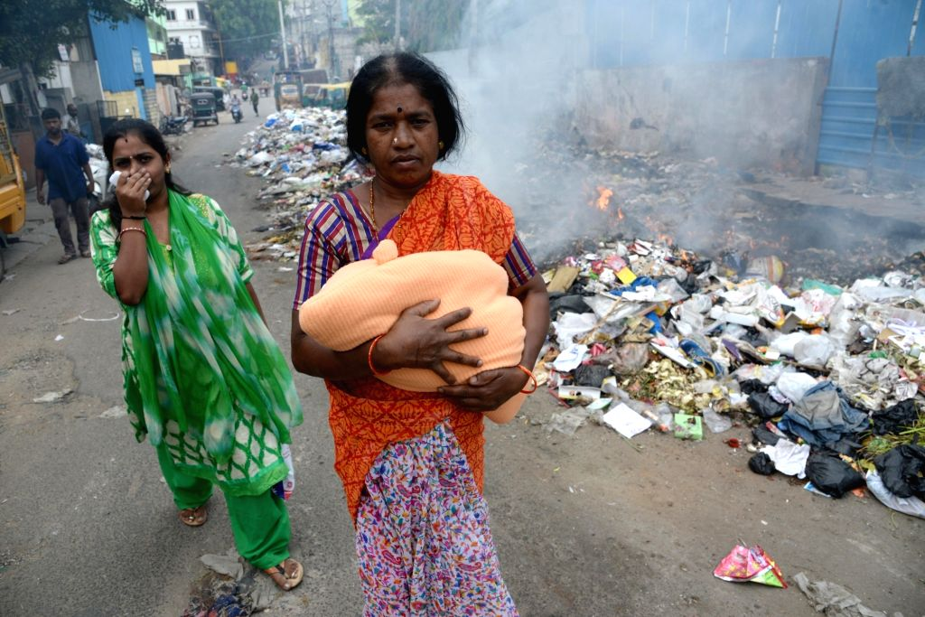 Women pass by a street where a pile of garbage is being burnt, in Bengaluru on June 5, 2018. June 5 is observed as World Environment Day.