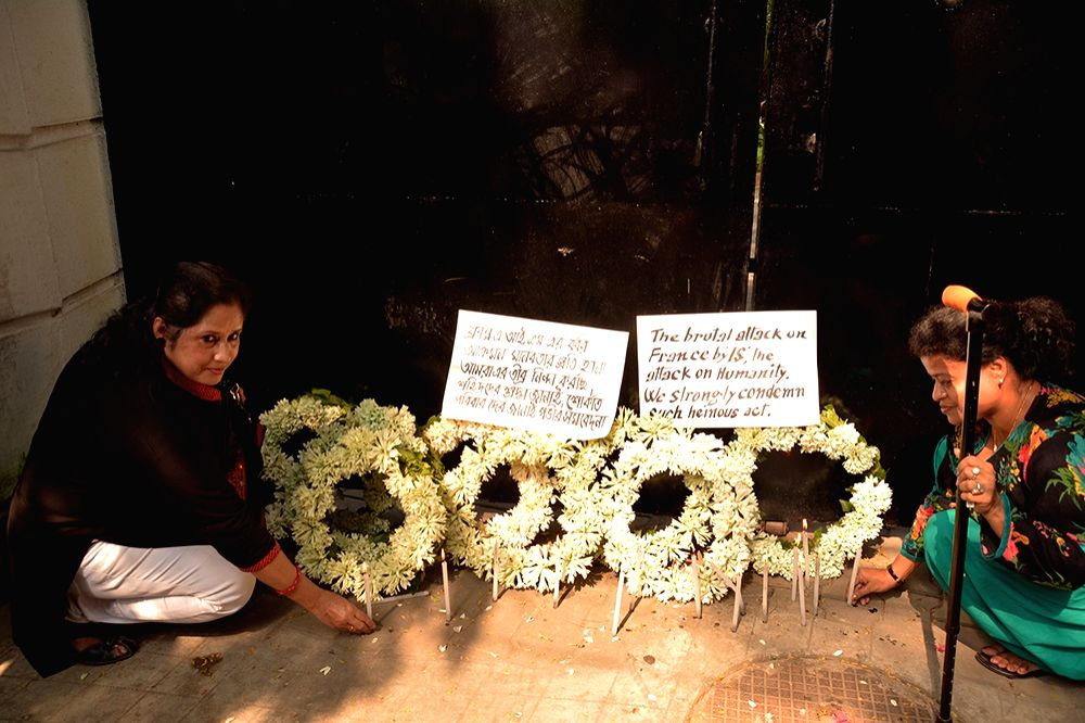 Women places flowers in front of the French Embassy consulate to mourn the victims of a series of attacks in Paris; in Kolkata on Nov 15, 2015.