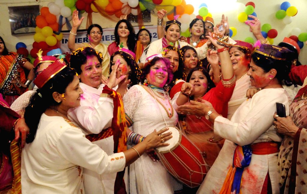 Women play with colours during a 'Holi Milan Samaroh' in Patna on March 10, 2017.