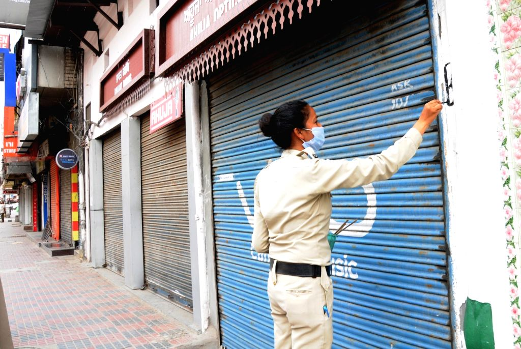 Women police personnel mark shops in Amritsar as per categories bifurcated by the district authorities so as to avoid confusion among traders over the opening of shops amid relaxations ...