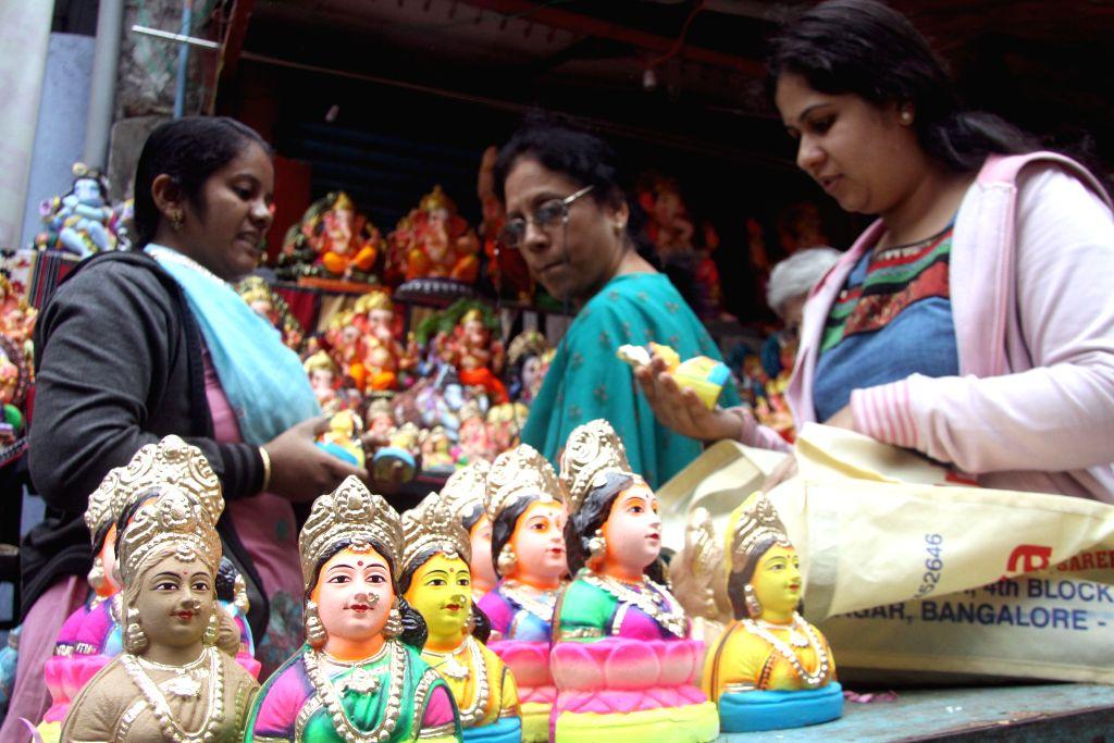 Women purchasing Gouri idols on the eve of Gauri Ganesha Festival at Malleshwaram in Bangalore on Aug 27, 2014.