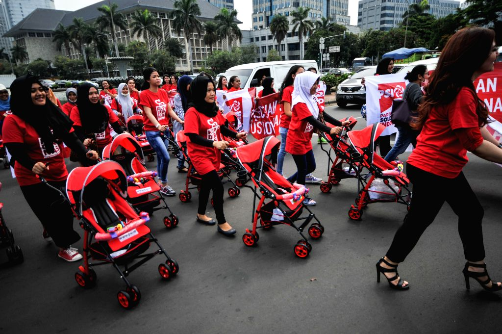 Women push their baby strollers across a street during a peaceful demonstration to raise awareness of policy makers on the importance of public facilities for women ...