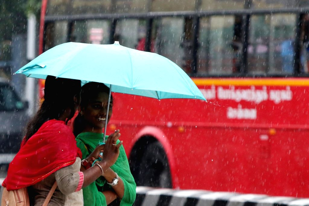 Women shield themselves with an umbrella during rains in Chennai on Oct 17, 2019.