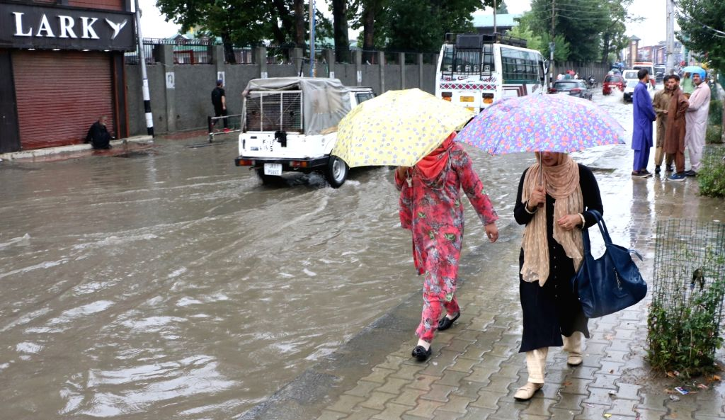 Women shield themselves with umbrellas as they walk past an inundated street during rains, in Srinagar on July 25, 2019.
