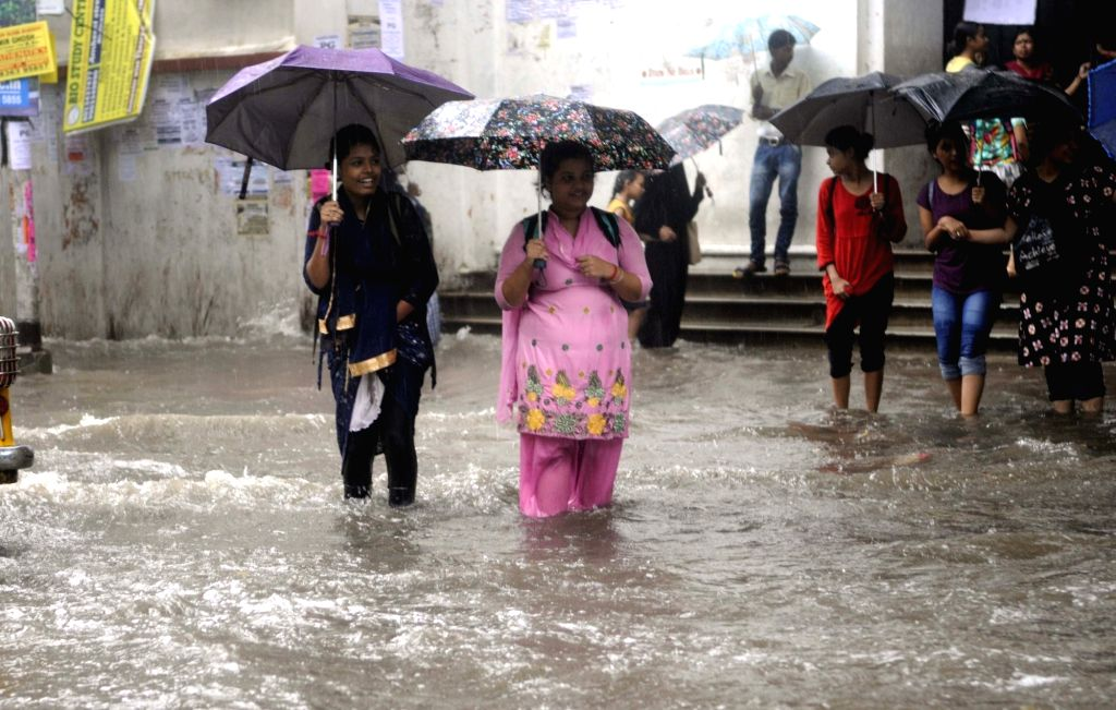 Women shield themselves with umbrellas during rains, in Kolkata on July 26, 2018.