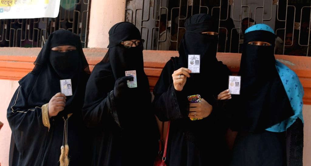 Women show their Voter ID cards as they arrive to cast their votes for the 2019 Lok Sabha elections, in Nagpur, on April 11, 2019.