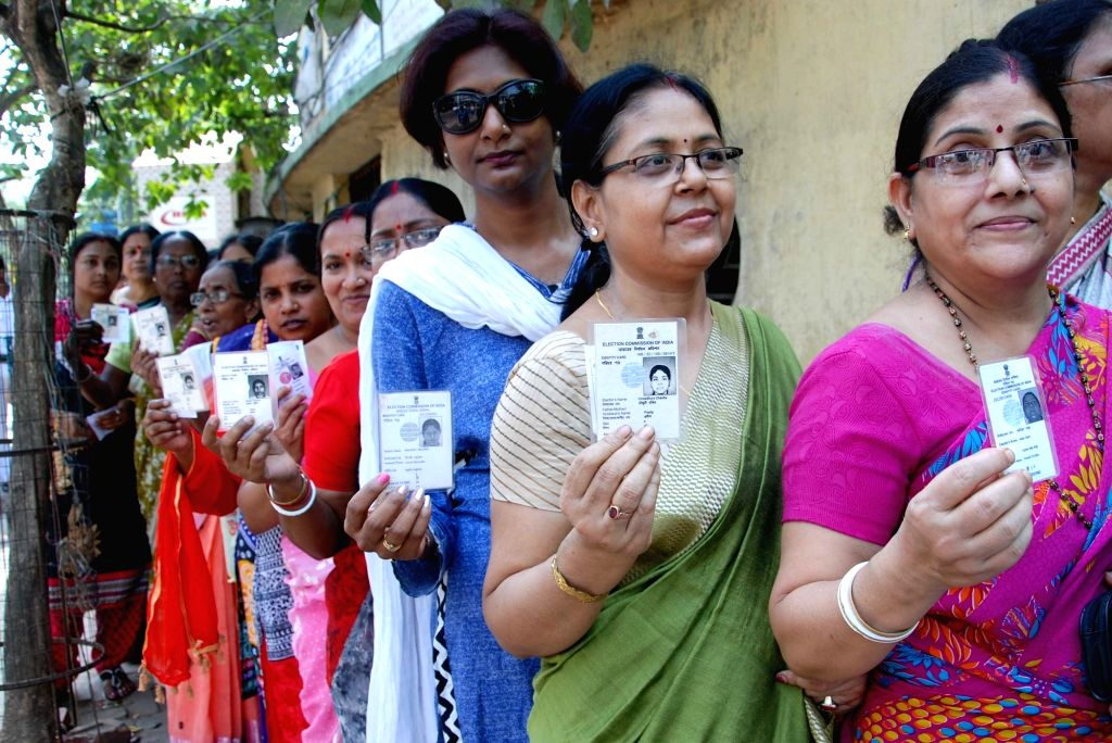Women show their voter ID cards as they wait in a queue to cast their vote at the polling station during the West Bengal Assembly Election in Kolkata on April 21, 2016.